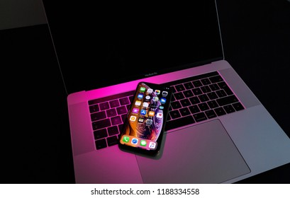 PARIS, FRANCE - SEP 25, 2018: New iPhone Xs and Xs Max smartphone model by Apple Computers close up. Newest golden Apple Iphone on pink magenta light on Macbook Pro 15 laptopkeyboard