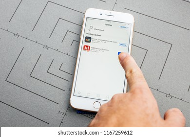 PARIS, FRANCE - SEP 26, 2016: Male hand holding New Apple iPhone 7 8 Plus smartphone after unboxing and testing by installing the app application software HSBC DEEZER Online banking apps purchased
