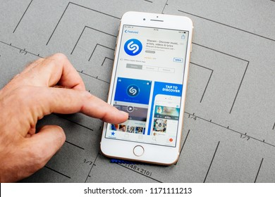 PARIS, FRANCE - SEP 26, 2016: Male hand holding New Apple iPhone 7 8 Plus smartphone after unboxing and testing by installing the app application software Shazam
