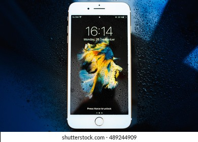 PARIS, FRANCE - SEP 26, 2016: New Apple iPhone 7 Plus unboxing and testing - locked iPhone covered with water drops. New iPhone7 is one of the best waterproof smart phone in the world