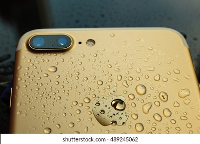 PARIS, FRANCE - SEP 26, 2016: New Apple iPhone 7 Plus unboxing and testing - pure gold iphone covered with rain water. New iPhone7 is one of the best waterproof smart phone in the world