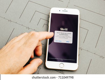 PARIS, FRANCE - SEP 26, 2016: Male hand holding New Apple iPhone 7 Plus after unboxing and testing by installing the app application software Skrill online payment app