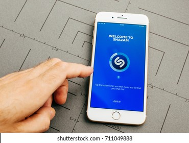 PARIS, FRANCE - SEP 26, 2016: Male hand holding New Apple iPhone 7 Plus after unboxing and testing by installing the app application software SHAZAM app on smartphone
