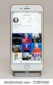 PARIS, FRANCE - SEP 26, 2016: New Apple iPhone 7 Plus in docking station after unboxing testing by installing app application software Instagram with hillary Clinton president candidate account feed