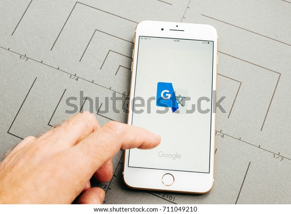 PARIS, FRANCE - SEP 26, 2016: Male hand holding New Apple iPhone 7 Plus after unboxing and testing by installing the app application software Google Translate