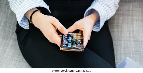 PARIS, FRANCE - SEP 27, 2018: Wide image of elegant woman testing the newest latest iPhone Xs and Xs Max smartphone telephone from Apple Computers on office living room sofa