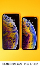 PARIS, FRANCE - SEP 27, 2018: Apple Computers iPhone Xs and Xs Max as hero object on bright glamorous modern neon pop orange background smartphone with home liquid wallpaper