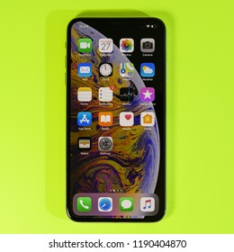 PARIS, FRANCE - SEP 27, 2018: Apple Computers iPhone Xs Max as hero object on bright glamorous modern neon pop yellow background - smartphone telephone with OLED display with all home apps square