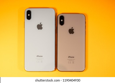 PARIS, FRANCE - SEP 27, 2018: Compare Apple Computers iPhone Xs and Xs Max as hero object on bright glamorous modern neon pop orange background - smartphone telephone Apple logo glass back