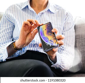 PARIS, FRANCE - SEP 27, 2018: business woman admiring the new silicone protection case for her latest iPhone Xs and Xs Max smartphone telephone from Apple Computers on office living room sofa