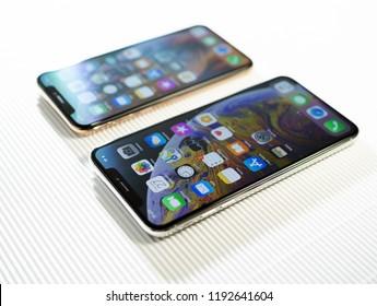 PARIS, FRANCE - SEP 27, 2018: Tilt-shift focus lens over two new Apple Computers iPhone Xs and Xs Max with home apps on the gorgeous OLED display on stripe cardboard background - side view