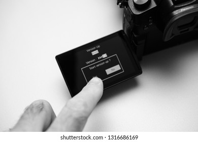Paris, France Sep 30, 2017: Man hand prearping to do the upgrade of firmware update process on the screen on modern Panasonic Lumix GH5 camera