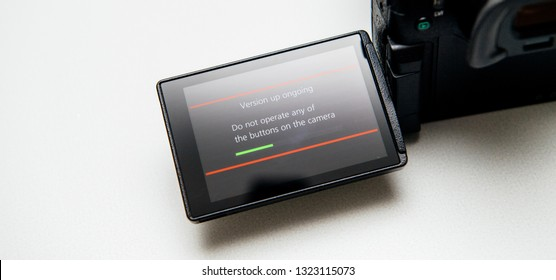 Paris, France Sep 30, 2017: Firmware update process on the screen on modern Panasonic Lumix GH5 message do not operate any of the button of the camera progress bar - white background