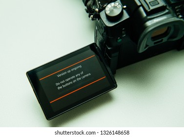 Paris, France Sep 30, 2017: Firmware update process on the screen on modern Panasonic Lumix GH5 message do not operate any of the button of the camera
