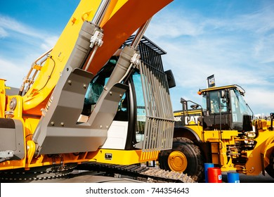 PARIS, FRANCE - SEP 5, 2014: Yellow Liebherr excavator and Cat tractor parked on a street near the construction site on a sunny day
