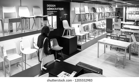 PARIS, FRANCE - SEP 9, 2017: View from above of French adult woman shopping for chairs furniture in the IKEA shopping furniture mall center black and white