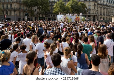 "PARIS, FRANCE - SEPT. 7, 2014: A big crowd cheers and dances during the ""lavage de la Madeleine"" (washing of Ste Madeline Church), a Brazilian festival in Paris."