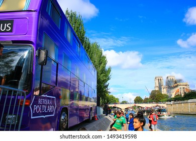 Paris, France. September 01. 2019: View of the knight bus, from the movie Harry Potter and the prisoner of Azkaban. Reproduction that welcomes thousands of fans to visit. Notre-Dame de Paris in back.