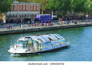 Paris, France. September 01. 2019: View of the knight bus, from the movie Harry Potter and the prisoner of Azkaban. Reproduction that welcomes thousands of fans to visit. Tourist boat in foreground.