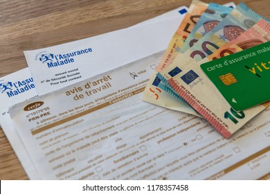Paris, France - September 07, 2018 : French document of sick leave, stoppage of work, with money and Vitale card