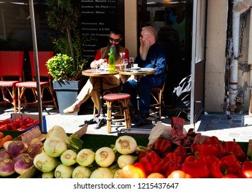 PARIS, FRANCE - SEPTEMBER 1, 2018: Beauvau street market. Two men sitting at cafe terrace at background. Parisian urban scene.