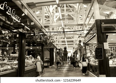 PARIS, FRANCE - SEPTEMBER 1, 2018:  People shopping at butchery and fish stalls at Beauvau food covered market, famous for various deli shops and beautiful wooden interior and hall decoration. Sepia.