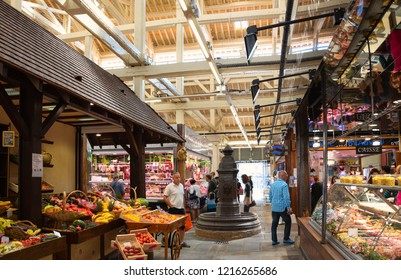 PARIS, FRANCE - SEPTEMBER 1, 2018:  Vegetables and fruits and butchery stall at Beauvau food covered market, famous for its various deli shops and beautiful wooden interior and hall decoration.
