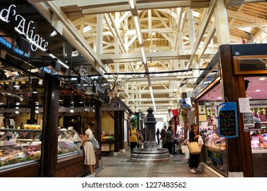 PARIS, FRANCE - SEPTEMBER 1, 2018:  People shopping at butchery and fish stalls at Beauvau food covered market, famous for its various deli shops and beautiful wooden interior and hall decoration.