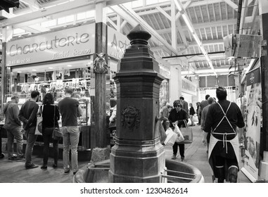 PARIS, FRANCE - SEPTEMBER 1, 2018:  People shopping at delicatessen stall at Beauvau food covered market, famous for various deli shops and beautiful wooden interior and hall decoration. Black white.