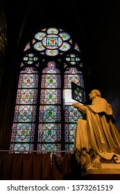 PARIS, FRANCE, SEPTEMBER 1, 2018 : Monk statue and stained window in the Notre Dame de Paris cathedral