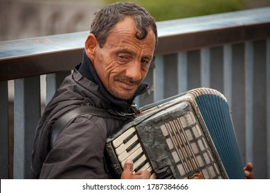 Paris / France - September 10, 2013: A smiling street musician plays the accordion for tips on a street corner in Paris, France.