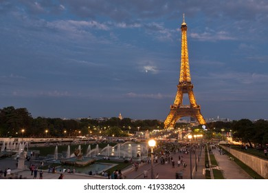 PARIS, FRANCE - SEPTEMBER 10: Artificially illuminated Eiffel tower with the rising moon in the background. Many people enjoyed the view to the Eiffel tower on September 10, 2011 in Paris, France.