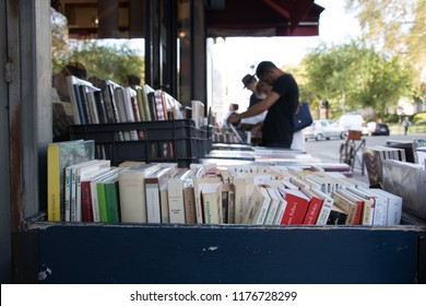 Paris, France - September 11, 2018: People checking the used French books at an outdoor stand bookstore in central Paris