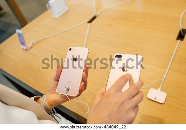 PARIS, FRANCE - SEPTEMBER 16, 2016: New Apple iPhone 7 being tested by woman after purchase - comparing the both iPhone 7 and iPhone 7 Plus photo camera.