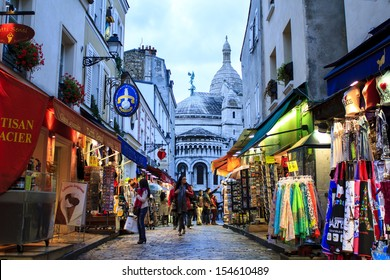 PARIS, FRANCE - SEPTEMBER 16 : Montmartre by twilight - shopping street near Sacre Coeur with tourists and Parisians walking around on September 16th 2013 in Paris, France