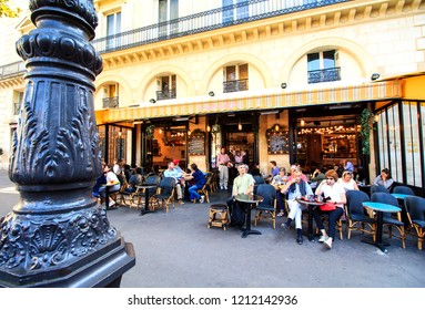 PARIS, FRANCE - SEPTEMBER 1st, 2018 : parisians and tourists relaxing in the typical open cafe terrace in Paris, France