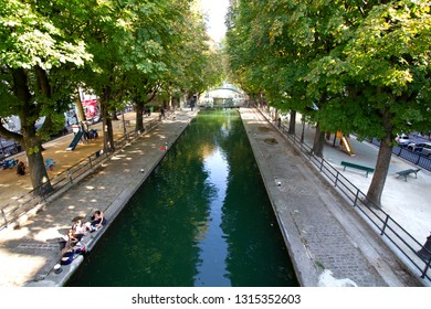 PARIS, FRANCE - SEPTEMBER 1st, 2018 : People sitting alongside Canal San Martin in Paris, enjoying summer under a shade of trees and freshness from the canal.
