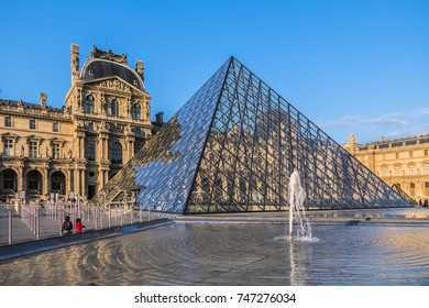 PARIS, FRANCE - SEPTEMBER 2, 2017: View fragments of Louvre buildings and pyramid in main courtyard (Cour Napoleon) of Louvre Museum. Louvre Museum is one of largest and most visited museums worldwide