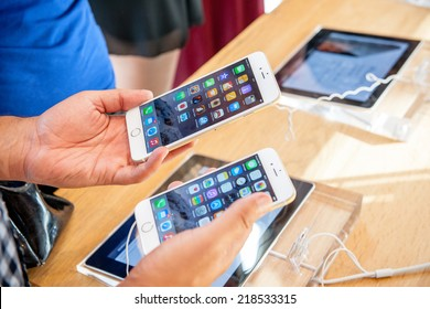 PARIS, FRANCE - SEPTEMBER 20, 2014: Man comparing the new Apple iPhone 6 and iPhone 6 Plus during the sales launch of the latest Apple Inc. smartphones at the Apple store in Paris, France