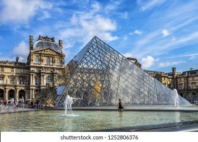 PARIS, FRANCE - SEPTEMBER 20, 2018: Cour Napoleon in Paris Louvre Museum: pyramid and Louvre Museum buildings. Paris Louvre Museum is one of largest and most visited museums worldwide.