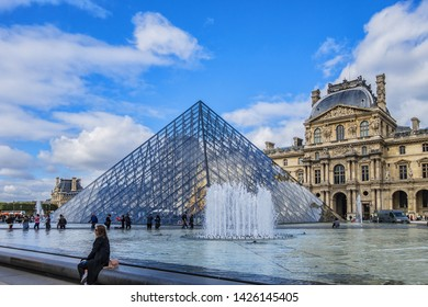 PARIS, FRANCE - SEPTEMBER 20, 2018: Main courtyard (Cour Napoleon) in Paris Louvre Museum: fountain and Louvre Museum buildings. Paris Louvre Museum - one of largest and most visited museums worldwide