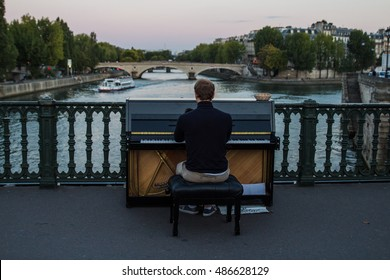 PARIS, FRANCE - SEPTEMBER, 2015: Music street performer boy playing on the piano against a river and sky background on the bridge.