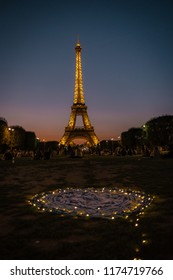 Paris france September 2018, happy young couple watching eifel tower at night, man woman picnic in the park with Christmas lights during sunset