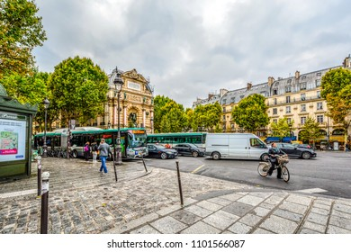 Paris, France - September 21 2017: A cloudy, busy morning in Place Saint-Michel in the 5th arrondissement of Paris France with the Fontaine Saint-Michel and busses, cars and bicycles