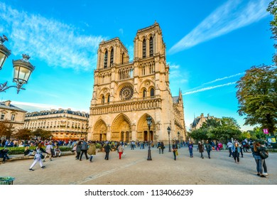 Paris, France - September 21 2017: Sunlight hits the gothic Notre Dame Cathedral on ile de la cite in Paris France with tourists enjoying a summer day on the Parvis Notre-Dame, or place Jean-Paul-II.
