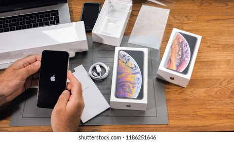 PARIS, FRANCE - SEPTEMBER 21, 2018: Apple fan boy unboxing latest Apple Iphone Xs Max and Xs flagship smartphone mobile phone model from Apple Computers first run of phone with Apple Logo on display