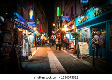 Paris, France - September 21 2018: Tourists pass shops and cafes as they walk the colorful neon streets late at night in the Latin Quarter section of Paris France