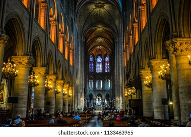 Paris, France - September 22 2017: Tourists visit the beautiful, colorful and solemn interior of the Notre Dame Cathedral in Paris France with stained glass windows and altar with cross and crucifix.