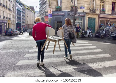 Paris, France - September 23, 2017: Two girls carry chairs through crosswalk