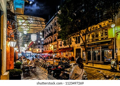 Paris, France - September 23 2017: Late night in the Latin Quarter of Paris as the shops and cafes light the street with a full moon overhead in Paris France